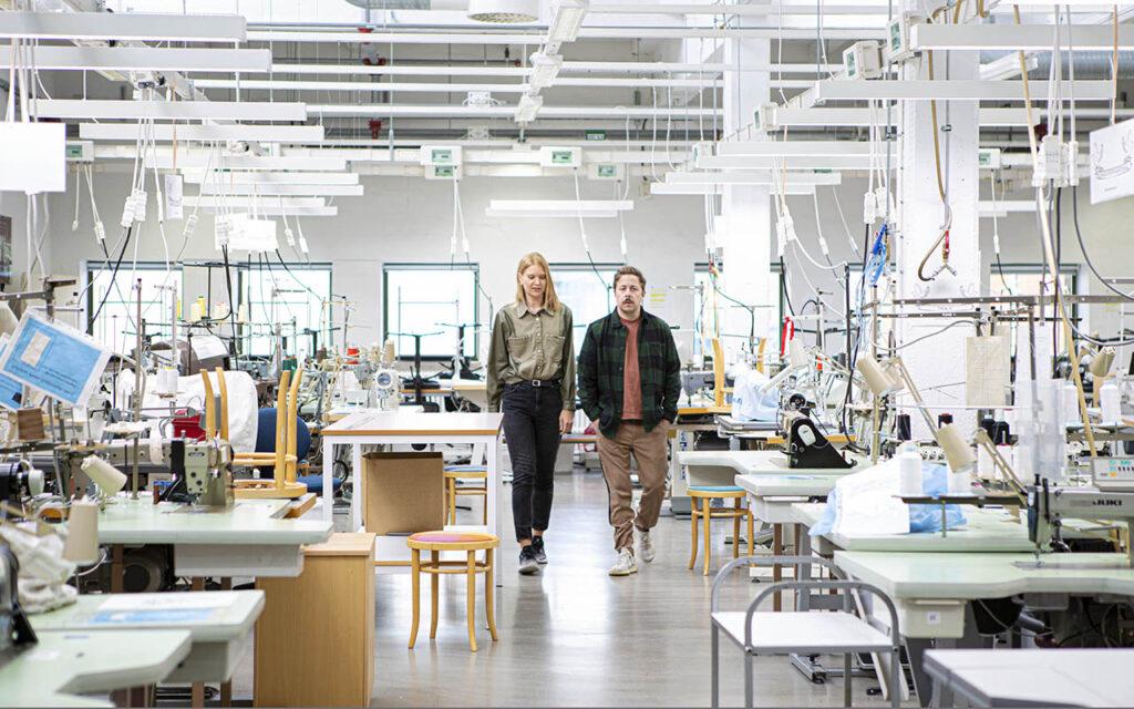 Kvinna och man går i en lärosal med symaskiner