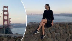 kvinna sitter på mur med benen i kors
