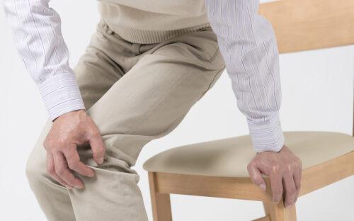 Äldre man med smärta i benen som reser sig från en stol